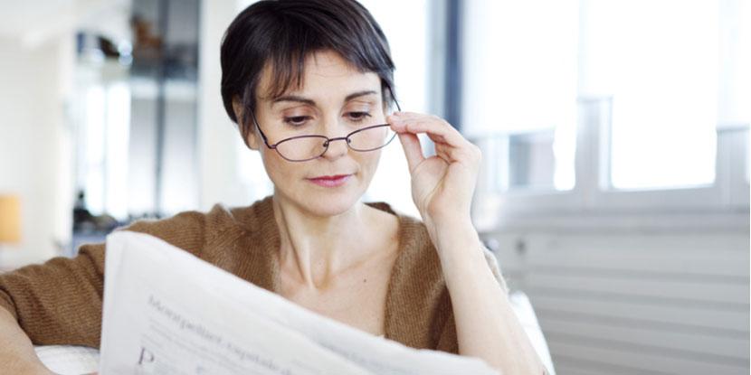 mulher usando óculos para presbiopia e lendo o jornal