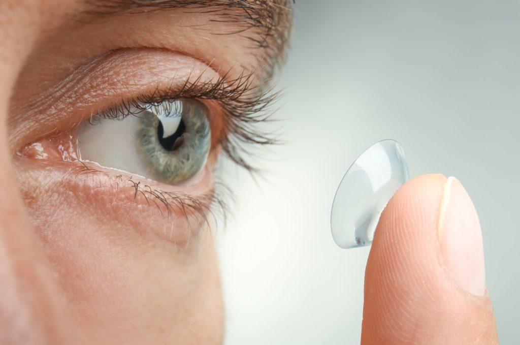 pessoa colocando lentes rígidas no olho