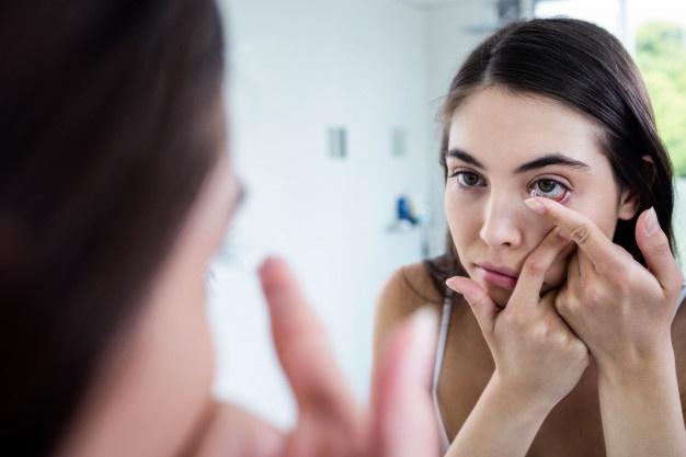 menina colocando lentes de contato em seu olho