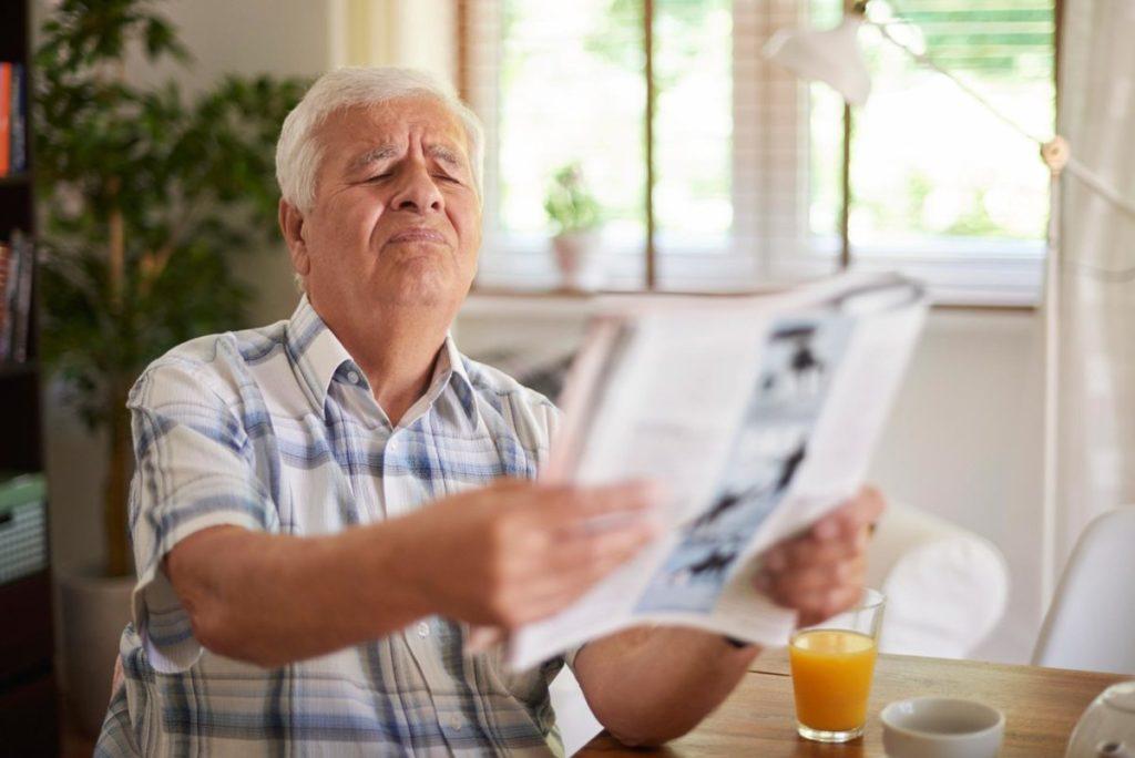 Homem com dificuldade para enxergar, precisando esticar o braço,e com presbiopia